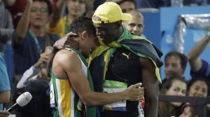Jamaica's Usain Bolt, right, winner of the men's 100-meter final embraces South Africa's Wayde Van Niekerk, winner of the men's 400-meter final during the athletics competitions of the 2016 Summer Olympics at the Olympic stadium in Rio de Janeiro, Brazil, Sunday, Aug. 14, 2016. (AP Photo/Julio Cortez)